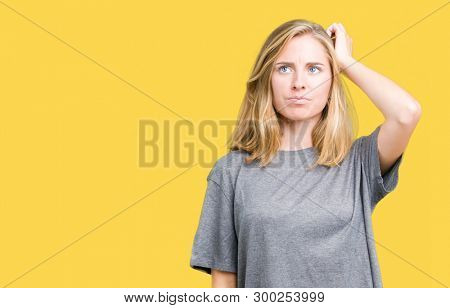 Beautiful young woman wearing oversize casual t-shirt over isolated background confuse and wonder about question. Uncertain with doubt, thinking with hand on head. Pensive concept.