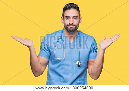Handsome young doctor surgeon man over isolated background clueless and confused expression with arms and hands raised. Doubt concept.