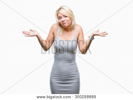 Young beautiful blonde woman over isolated background clueless and confused expression with arms and hands raised. Doubt concept.