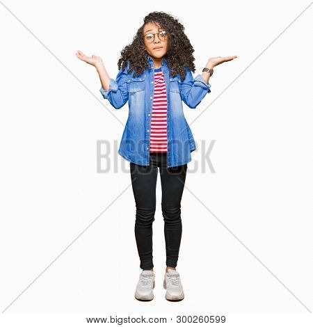 Young beautiful woman with curly hair wearing glasses clueless and confused expression with arms and hands raised. Doubt concept.