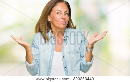Middle age adult woman wearing casual denim shirt over isolated background clueless and confused expression with arms and hands raised. Doubt concept.