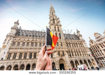 Woman Tourist Holds In Her Hand A Flag Of Belgium Against The Background Of The Grand-place Square I
