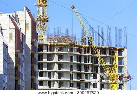 Finished Apartment Building And A New High-rise Building Construction Site With Yellow Cranes Agains