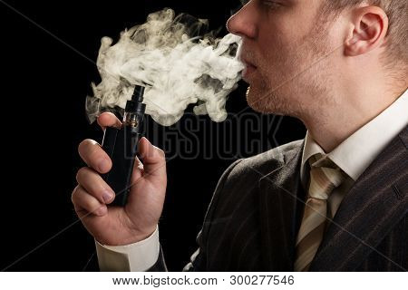 Business Man With The Electronic Cigarette And Steam Isolated On Black Background