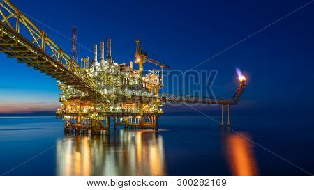 Offshore Oil And Gas Central Processing Platform In Sun Set Which Produce Raw Gas, Crude And Hydroca