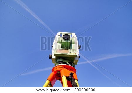 Total Station With Blue Sky In The Background. Survey Instrument Geodetic Device, Total Station Set