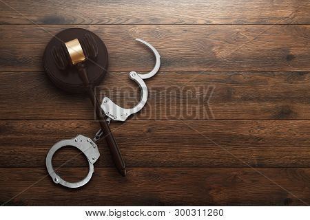 Judge's Gavel And Handcuffs On Wooden Background, Top View, Flat Lay. The Concept Of Justice, Punish
