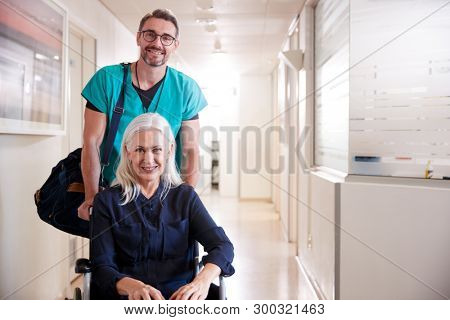 Male Orderly Pushing Senior Female Patient Being Discharged From Hospital In Wheelchair