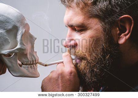 Man Smoking Cigarette Near Human Skull Symbol Death. Nicotine Destroy Health. Harmful Habits. Smokin