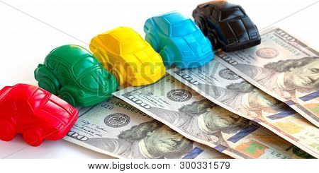 Concept Cars And Money. Little Toy Car Mock-ups And Dollars Banknotes On White Table. Buying, Rentin