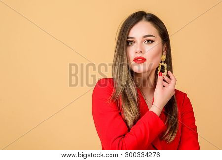 poster of Woman wear glamorous earrings. Fashion trend. Jewelry shop. Girl model long hair demonstrating golden jewelry earrings. Expensive accessory. Fashionable jewelry. Impeccable makeup and perfect jewelry