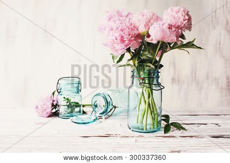 Beautiful Pink Peony Flowers In An Antique Blue Mason Jar Over A White Rustic Wood Table Background