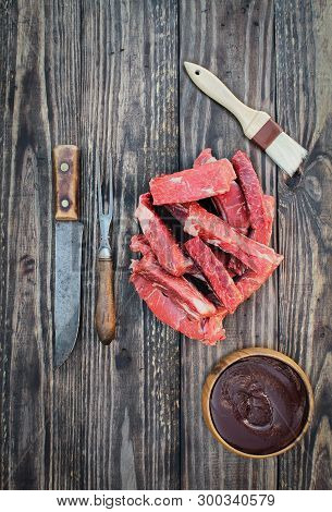 Uncooked Raw Boneless Country Short Ribs With Bbq Sauce, Brush, Vintage Meat Fork And Knife Over Top