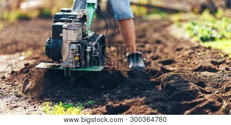 Close Up Photo Of Young Farmer Gardener Cultivate Ground Soil Rototiller , Tiller Tractor, Cutivator