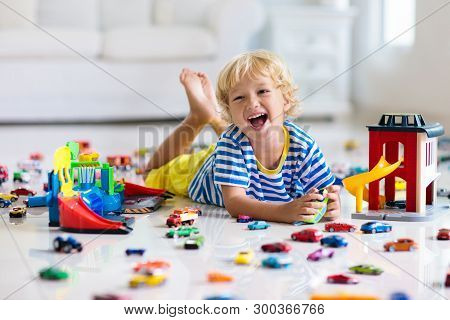 Kids Play With Toy Cars In White Room. Little Boy Playing With Car And Truck Toys. Vehicle And Trans