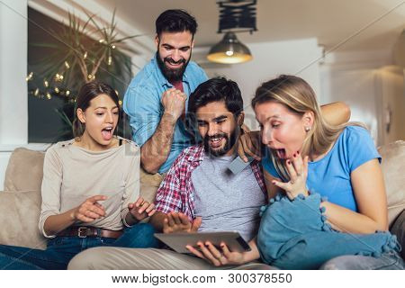 Four Casual Happy Friends Laughing Shopping Online Together In A Tablet Sitting On A Sofa In The Liv