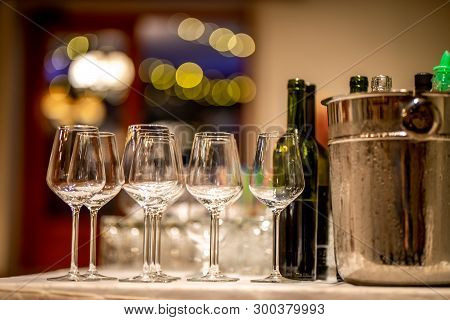 Empty Glasses, Wine Bottles And Bucket With Ice On Table In Restaurant. Ice Bucket, Wine Glasses And