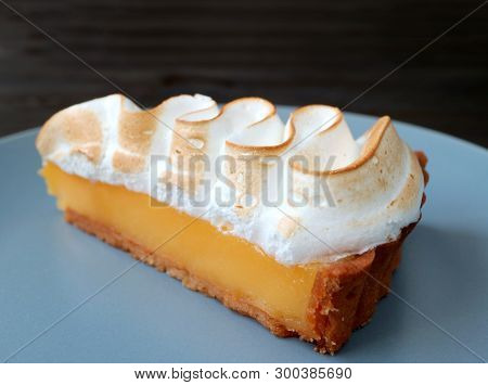 Closeup A Slice Of Mouthwatering Lemon Meringue Tart On A Blue Plate