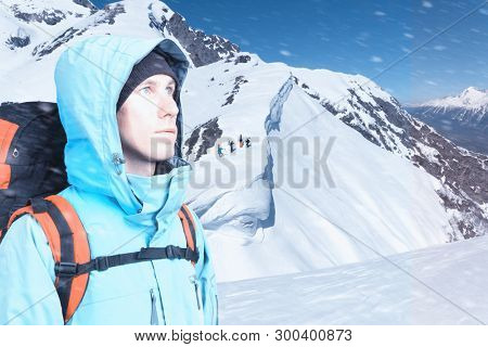 Adventurous young man with backpack standing on mountain top view and looking out. Snowboarders walking uphill for freeride, extreme sports.