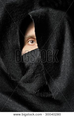 Eye of male looking from black fabric