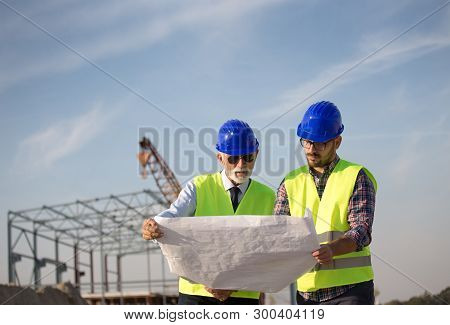 Two Engineers Talking At Building Site With Metal Construction In Background