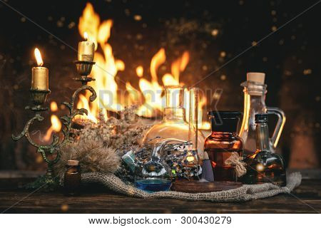 Alchemist Or Witch Doctor Table. Magic Potion Bottles And Dried Herbs On A Table On A Burning Fire B