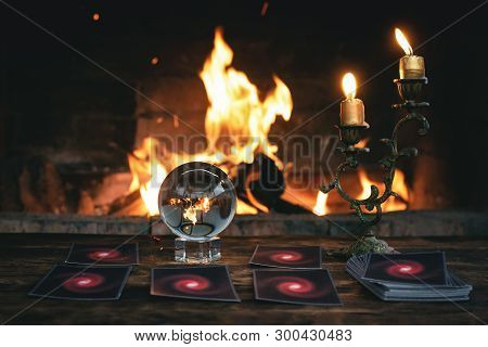 Tarot Cards And Crystal Ball On Fortune Teller Table On A Burning Fire Background. Futune Reading Co