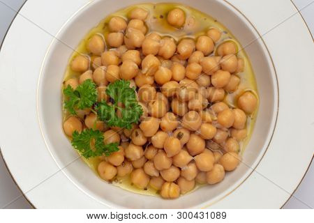 Greek chickpea soup (revithia soupa) garnished with parsley. It's made with olive oil, onion, water, oregano, garlic, bay leaf, lemon juice, flour and seasonings