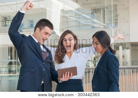 Three Good Looking Colleagues Standing  In Office Corridor, Man And Woman In White Blouse Exulting,