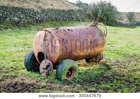 A Disused And Dilapidated Slurry Tanker With Punctured Tyres Sits Abandoned In A Muddy Field In The