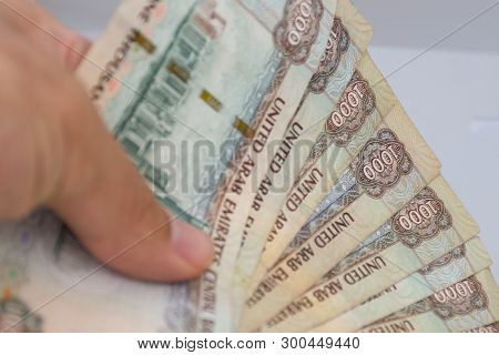 Persons Hand Giving The Currency Of The United Arab Emirates (uae) - Thousand Dirham Notes Spread Ou