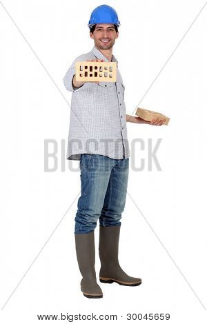 Man wearing a safety hat and showing a brick