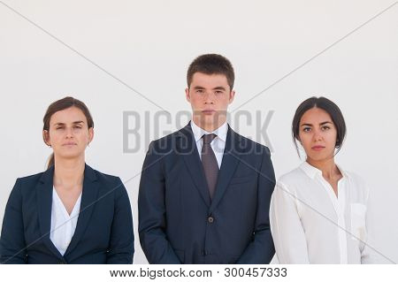 Corporate Portrait Of Serious Successful Business Team. Three Young Business People Standing For Cam