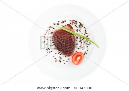 main entree : roasted beef lamb steak served with red tomato allspice peppers green chives on plate isolated over white background