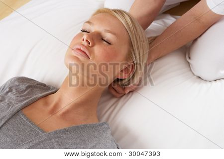 Woman having Shiatsu massage to head