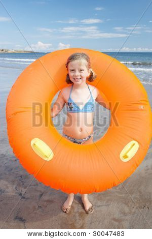 Child on beach with giant rubber ring