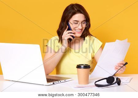Portrait Of Woman Talking On Smartphone And Holding Papers. Lady Calls On Mobile Phone, Works In Off
