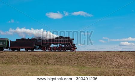 The Locomotive Rides On The Way To A High Mound. From The Pipe Of The Locomotive Is White Steam. The