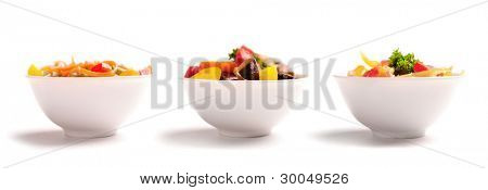 Different vegetable salads on plates on white background.