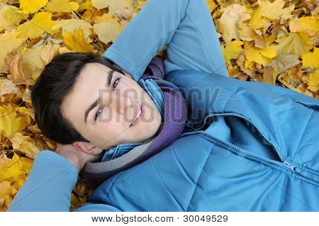 Young stylish man portrait laying in foliage in autumn park. Outdoor.