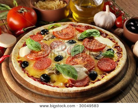 Pizza with ham, pepper and olives on wooden board