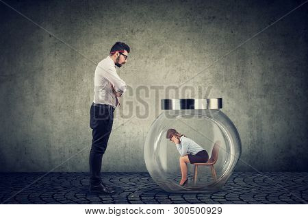 Authoritarian Angry Boss Businessman Looking At A Glass Jar With Captured Woman Inside