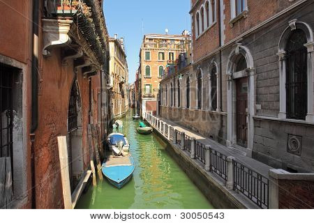 Horizontal image of small narrow canal with boats among old historic houses in Venice, Italy.