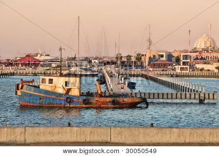 Old rusty fishing ship float on water surface in marina on Mediterranean sea, Israel.