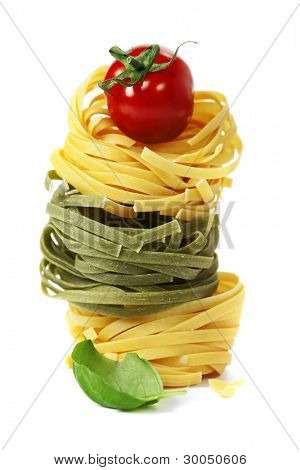 Italian pasta fettuccine nests with tomato and basil  isolated on white background