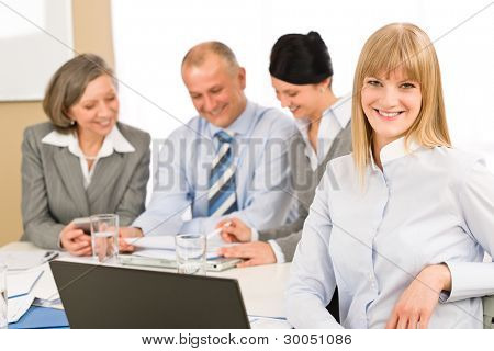 Businesswoman smiling at team meeting with colleagues