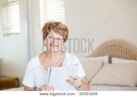 happy senior woman sitting on bed and reading newspaper