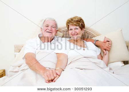 happy senior couple in bed relaxing