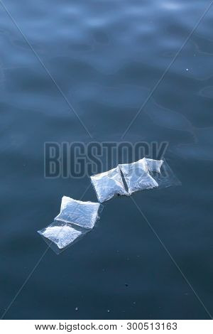 Plastic Marine Pollution, Underwater Plastic Bags And Packaging Floating Semi Submerged At Surface O