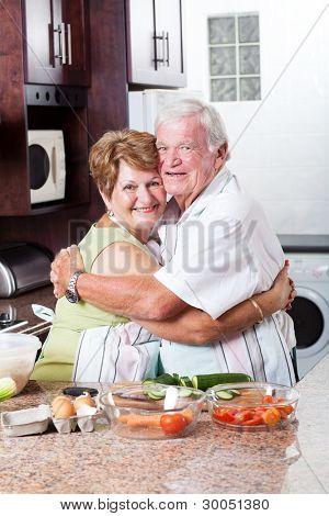happy loving senior couple hugging in kitchen